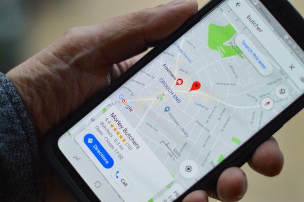 L'application Google Maps sur un smartphone tenu par quelqu'un.